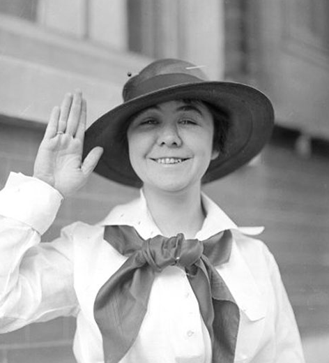 Smiling Loretta Walsh in Uniform with her hat at an angle and her hand raised as if she's taking an oath