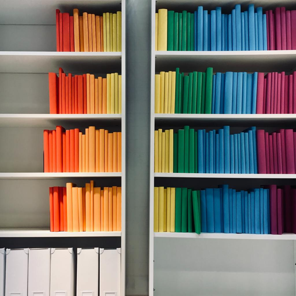 Books arranged on shelves by color like these is one way to Make Your Library a Subject of Bookshelf Envy