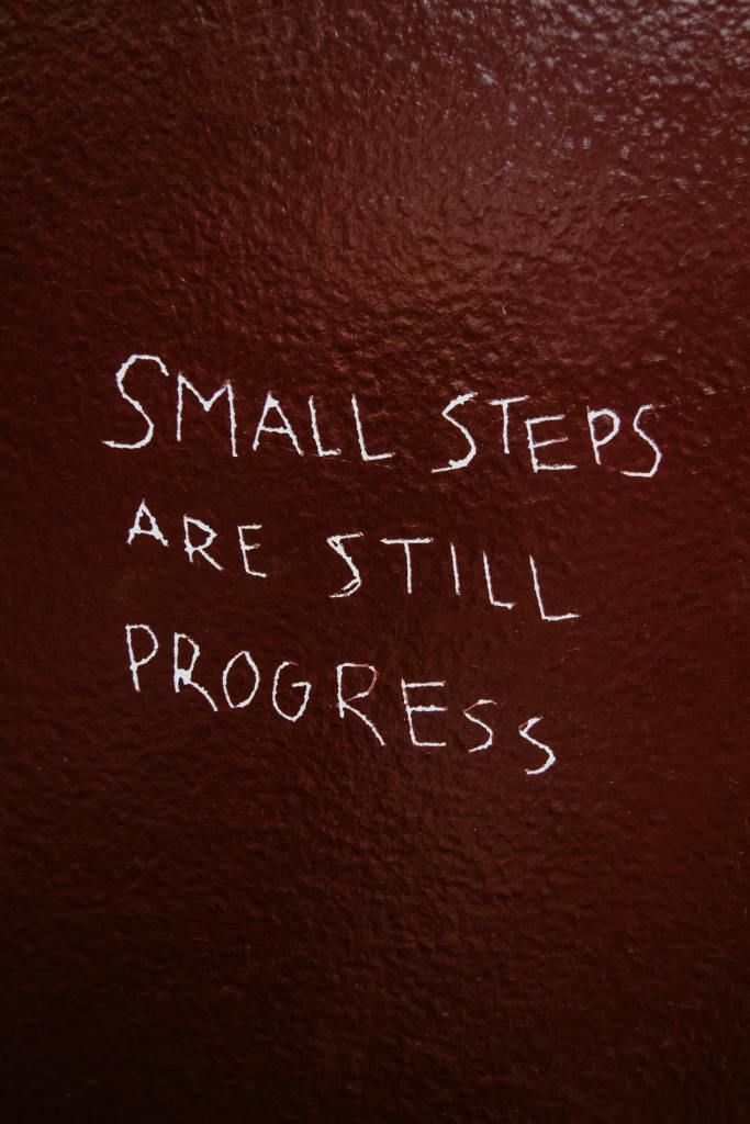 """hand written message on pebbly brown surface for when your motivation needs a boost says """"small steps are still progress."""""""