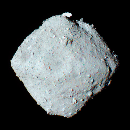 a view of the asteroid Ryugu --the asteroid appears to be a rounded cube with lots of rocks and pebbles on it--is the truth in asteroid dust?