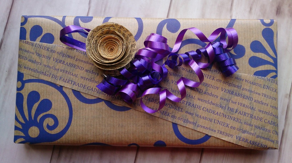 a package creatively wrapped in brown paper with curley q's in blue on the paper and with a paper flower and purple and blue curly ribbon