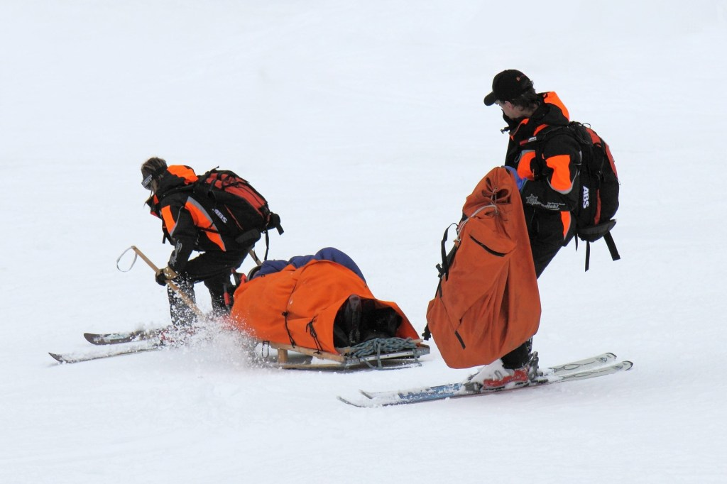 image of two ski patrollers taking an injured person downhill on a sled-One of the First Women on the National Ski Patrol