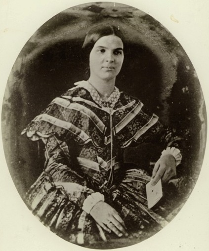 black & white image of Susan Shelby Magoffin in a dress and seated. She is holding something that may be an envelope.