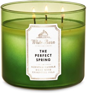 Image of green candle in a wide glass jar labeled white barn's the perfect spring. Enjoying spring's scent is one way spring cleaning can increase your creativity.