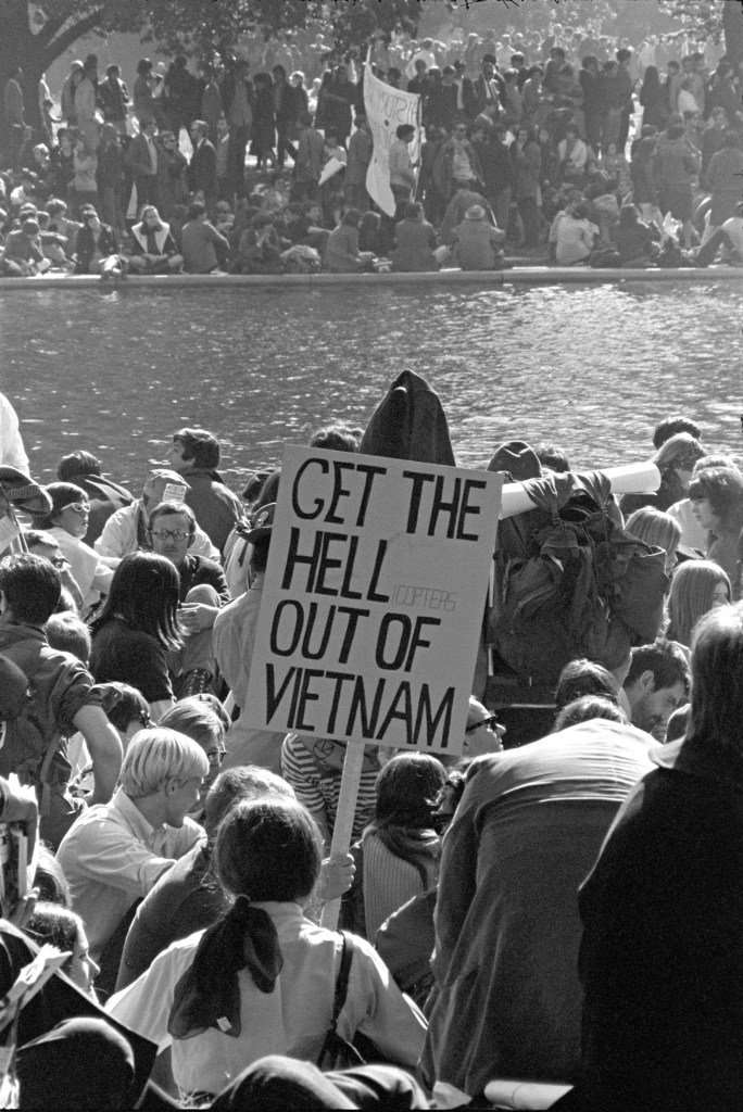 """Photograph of protestors on two sides of a river. A protest sign """"get the hell out of Vietnam"""""""