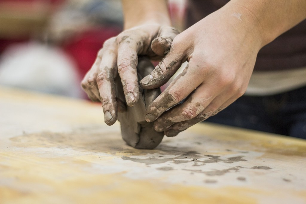 image of a pair of hands working wet clay