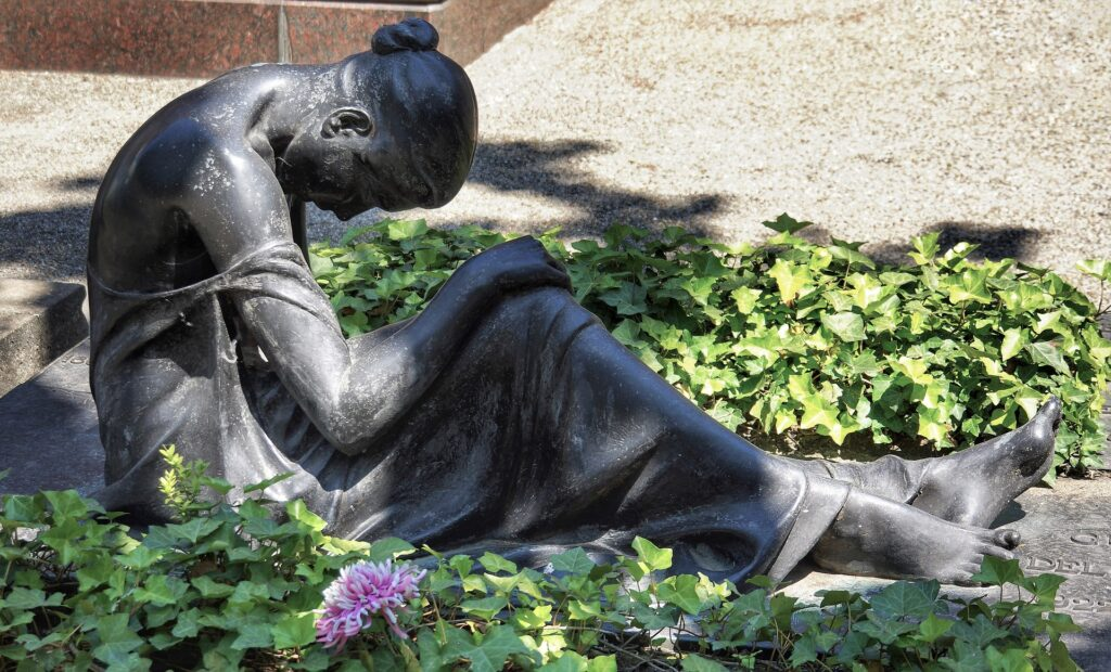 Photograph of a bronze statue of a woman sitting on the ground and bent over in grief because being a widow sucks.