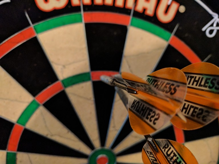 Photo of a dart board with darts in the second ring--not one bulls eye but a never give up-never surrender attitude keeps me going.