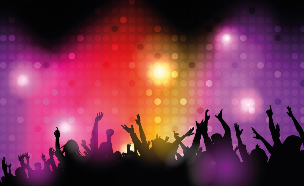 Photograph over the heads and upraised arms of a crowd against diffuse colored lights --give yourself the gift of joy