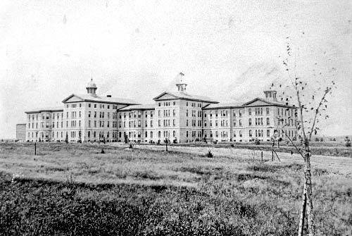 black and white photograph of an 5 storied white insane asylum with multiple connected buildings.