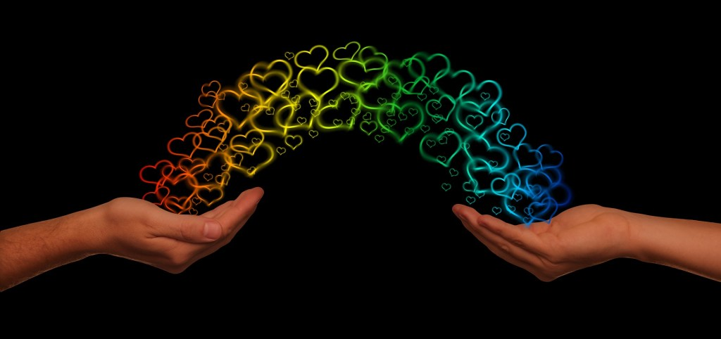 Image of a rainbow of heart shared from one hand to another a visual representation of a good deed brightens your day