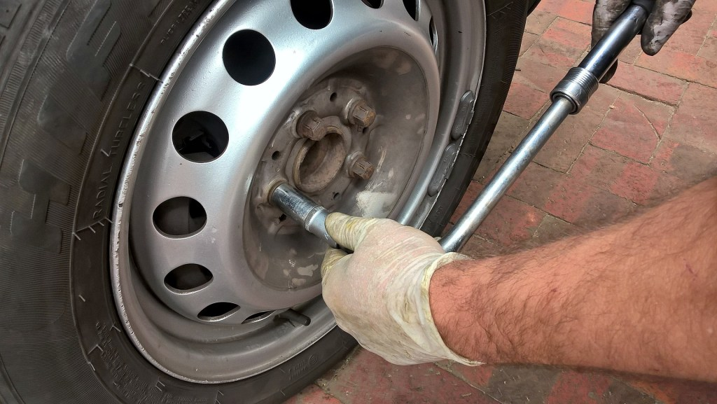 Image of a man's hands using a wrench on the lug nuts of a tire