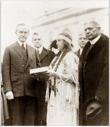 Image of President Coolidge and Rev. Sherman Coolidge, and Muskrat Bronson presenting the volume of Red Man. Her story is missing from our history books.