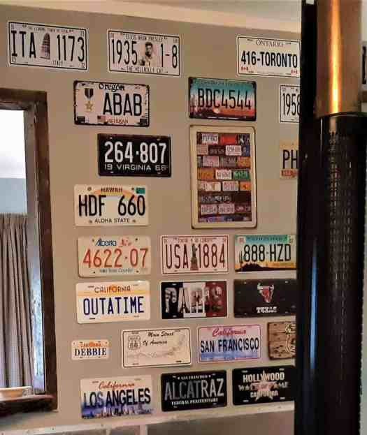 Wall featuring many hanging car registration plates.