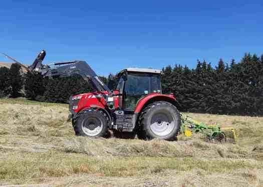 The tractor fluffing up rows of hay with the hay-bob in perfect, sunny haymaking conditions.