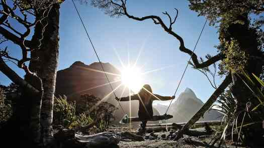 Mel Jubb on a makeshift swing with the sun behind her at Milford Sound.