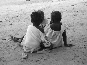 Two African children sit on the ground.