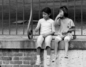 A boy and a girl, about 10 years old, dangle their feet over a ledge at the edge of a walkway through a city park.