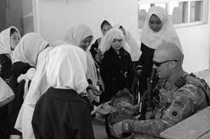 A group of Afghani school girls surround a National Guardsman wearing camouflage gear.