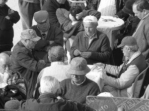 A group of older men sit in the sunshing playing cards.