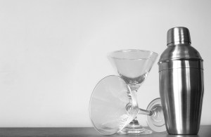 Two martini glasses, one upright, the other on its side, and a martini shaker.