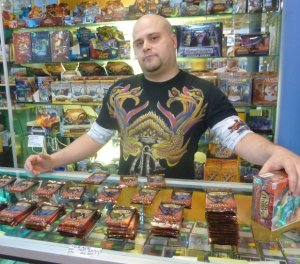 Mike Martins, proprietor of a card and game shop in Vancouver, stands in his shop surrounded by a good time.