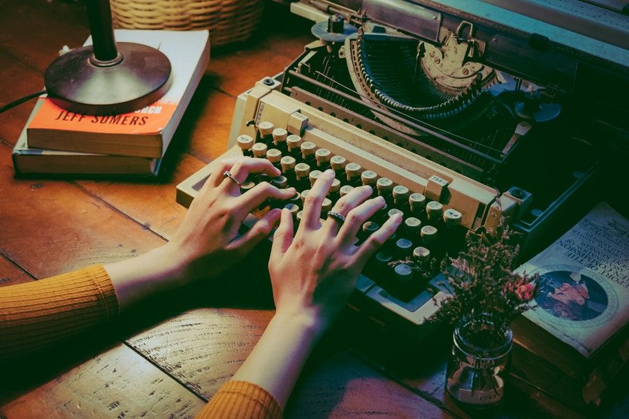 A pair of hands typing on a manual typewriter