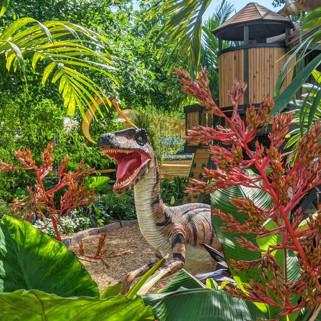 Model velociraptor in a display of tropical plants.