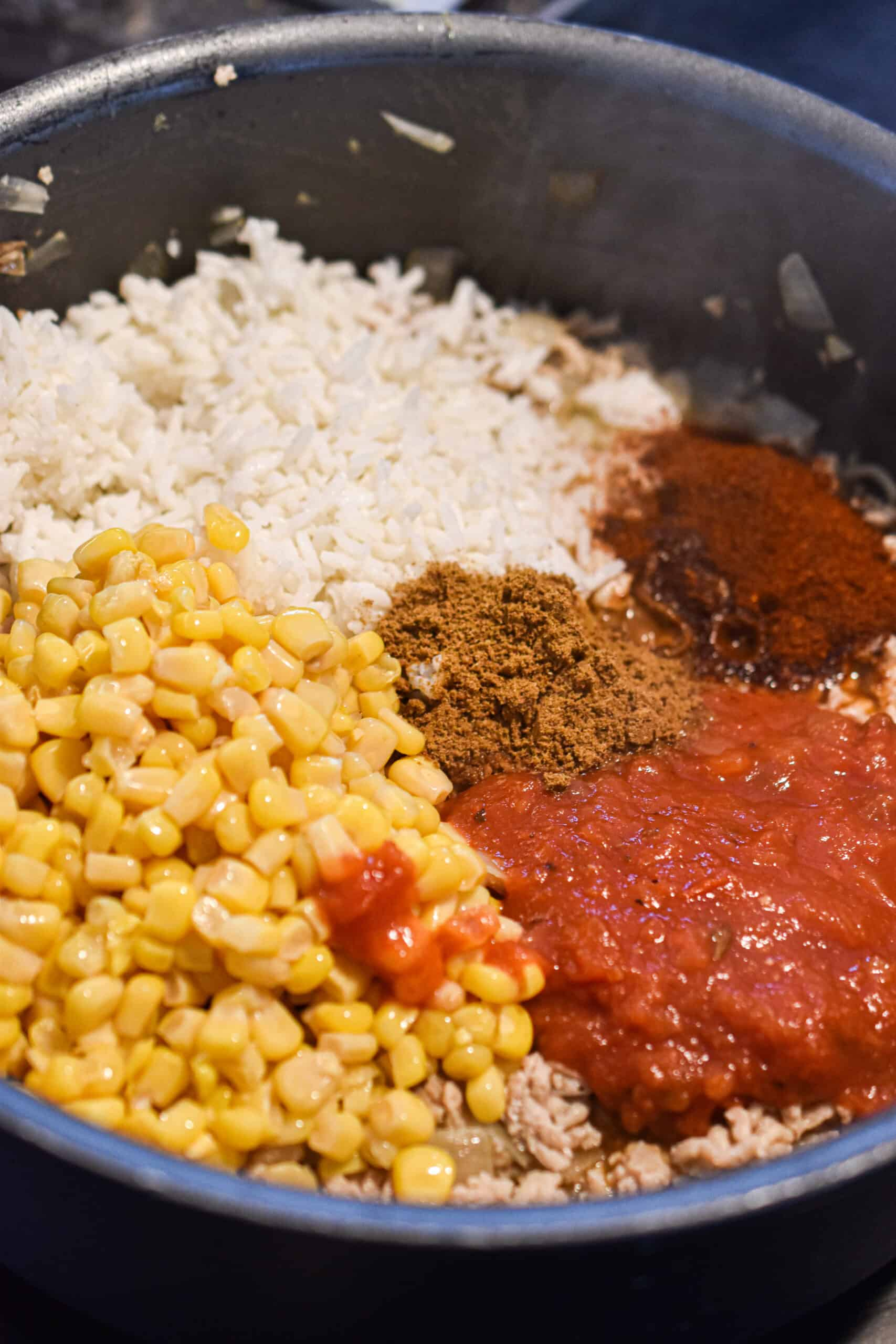 Cook the ground chicken, rice, corn, and spices together