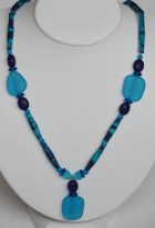 Necklace of blue and turquoise fabric beads and turquoise recycled glass