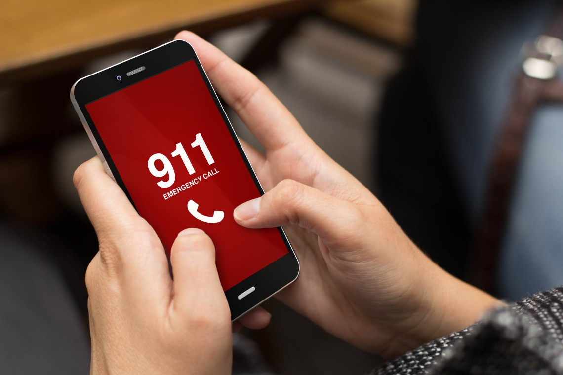 Hands dialing 911 on cell phone