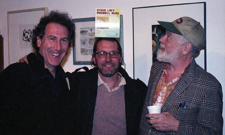 Dr Steven Feld (anthropologist & trombonist) and Tom Guralnick (concert presenter) and Roswell Rudd ---- March 20, 2000 ----- photo by Mark Weber (that's an advertisement for Steve Lacy & Roswell's recent cd on Verve on top of Tom's head)