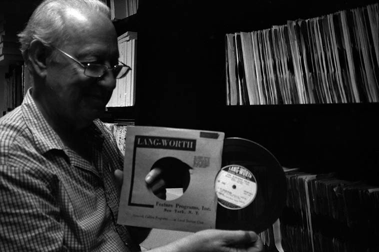Dan Morgenstern in the stacks at Institute of Jazz Studies, Rutgers University, Newark,  holding an actual Lang-Worth radio transcription disk from the 1940s, probably a Boyd Raeburn ----  photo by Mark Weber -- August 9, 2o11