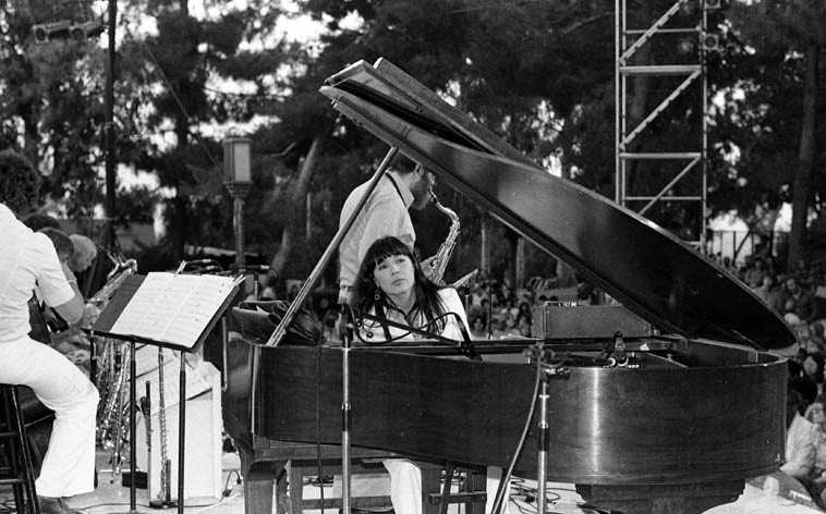 Toshiko Akiyoshi in Barnsdall Park -- August 4, 1977 ---- photo by Mark Weber ---- I'm going  to play a track from her trio album DEDICATIONS cut only 4 months previous to this shot and it's  a beaut (the Lp) where Toshiko is looking into a lot of things associated with Miles during his Blue  Note period (1952-1953 and earlier)(Barnsdall Park is a special place, situated on a small hill  at the furthermost eastern part of Hollywood: You drive east from the 101 down Hollywood  Blvd toward the Los Feliz arrondissement -- inside the Park on the hilltop is the Frank Lloyd Wright Hollyhock House, 1919)