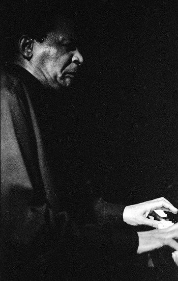 """Abdullah Ibrahim at the old Iridium on 63rd Street & Broadway -- July 1, 1997 -- Even though we arrived early enough to have dinner, mine was served just as the trio took the stage: What was I to do? I was practically sitting at Abdullah's elbow: Hog down while he began his first set? Duet for piano + pig? I don't think so. After his set Abdullah stepped down and over to our table and pointing at the plate where my curds & whey had gone cold, said: """"You didn't eat?"""" I said: Your music was enough for now, maestro, thank you ---- photo by Mark Weber -- his music is a form of trance music"""