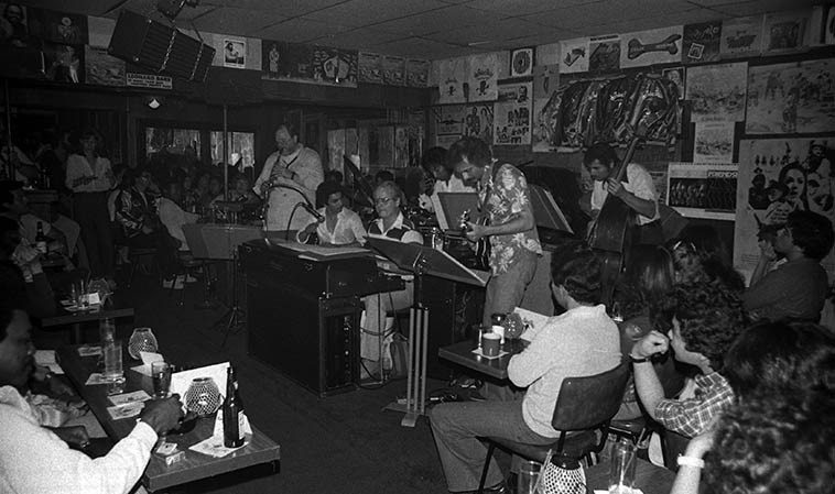 "Clare Fischer Salsa Picante: Gray Foster, soprano saxophone; Roland Vasquez, drums; Hector Andrade, conga; John Chiodini, guitar; Oscar Meza, bass, Clare Fischer, keyboards -- at The Baked Potato, North  Hollywood -- June 8, 1980 -- photo by Mark Weber ---- the other day I got caught up in the sheer gorgeous beauty of Clare's album ON A TURQUOISE CLOUD (2oo1) with his Clarinet Choir (9 clarinets with rhythm section and a couple brass and our old friend Cip on bass-clarinet!  And always Gary Foster on saxophone  interludes and clarinets) -- We'll listen to the title track today, a 1947 composition by Duke Ellington,  as well, listen to other versions of ""On A Turquoise Cloud"" by Jimmy Jones, Dick Hyman, Duke Ellington  Orchestra, and Scott Robinson."