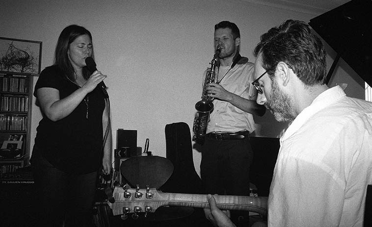 Cheryl Richards: jam session at Carol Liebowitz's studio -- September 4, 2o15 -- among the participants that afternoon coincidentally these three realized they were all there, of whom made Cheryl's recent release IF NOT FOR YOU (New Artists Records), so they sang a few for us -- Nick Lyons, saxophone, and Adam Caine, guitar -- photo by Mark Weber lounging on the sofa