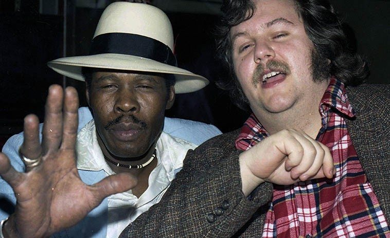 Mississippi Smokey Wilson and the new Friday KUNM noon jazz host John Breckow (Dig those sideburns!) -- January 14, 1978 at Pioneer Club, 88th & Vermont, Los Angeles -- photo by Mark Weber ----- Smokey could tear a Stratocaster apart, just bring down thunder & lightning in that blues tavern of his down in South Central, it was a beer & wine joint with a pool table and a lot of atmosphere, he kept a bottle of Johnny Walker Red stashed for me when I showed up, and a couple pistols and a rifle under the bar (I can probably tell people now but his secret hideaway of cash was kept under the pool table, you could lift up the green turf and there was the cash) ---- John & wife Dory moved to Corrales two years ago, he put in 25 years of radio on KPFK becoming part of late-night jazz history in Los Angeles, it's going to be a kick to hear him again, we were old running buddies back in those crazy days, there was so much going on in Los Angeles . . . .