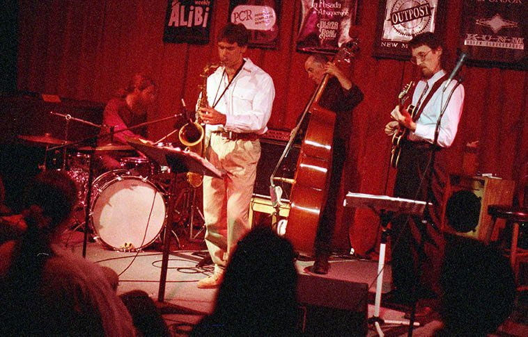 Real Time Quartet at old Outpost -- October 7, 1996 -- Kanoa Kaluhiwa (tenor), John Bartlit (drums), David Parlato (subbing on bass for Mark Tatum), Lewis Winn (guitar) -- photo by Mark Weber (Cal Haines was the original drummer in this band but he moved to Southern California just before this photo was taken, to take a job with Rockwell in Newport Beach for ten years) Lewis is one of those guys if the note he's looking for isn't on the guitar he just reaches up in the middle of a solo and de-tunes until he finds it (usually a low note): blarng, blaaaaarng, narng. He's also the guy that told me that our front porch wind chimes is Gmaj7+13dim4 or some such chord (I forgot which) Of all the musicians that have been in & out of Studio 725 he's the only one who has point that out.