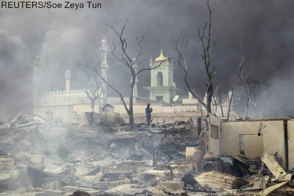 A man stands in front of a mosque as it burns in Meikhtila, March 21, 2013