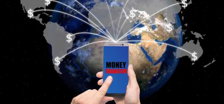 A person using a smartphone to transfer money to various points all over the world