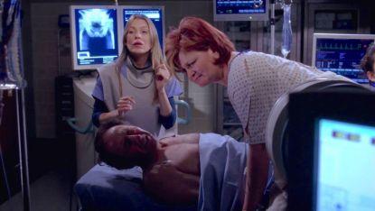 Meredith Grey aparece al fondo de la imagen. Delante de ella está un hombre tumbado con una mujer encima suya.