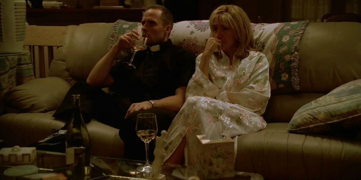 carmela soprano and father phil are watching a movie at the soprano house.