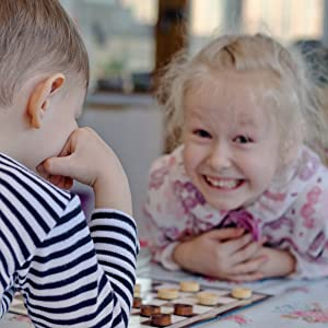 checkers children playing the old fashioned wholesome boardgame girl is smiling at camera boy