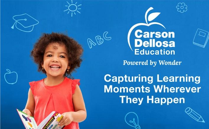 A preschool girl holding a workbook with the Carson Dellosa slogan