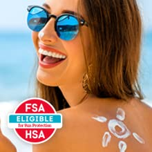 Woman smiling at the beach - Face and body sunscreen spray can be covered by FSA & HRA accounts