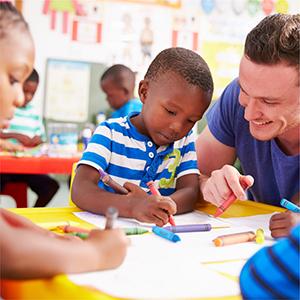teacher inside of a classroom helping preschool students with activities