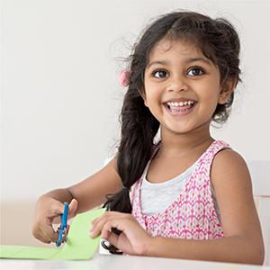 a preschool girl working on scissors skills cutting a piece of construction paper