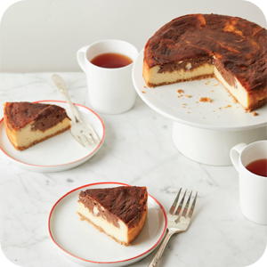 Image of cheesecake on table with fork and tea.