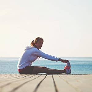 active woman stretching muscles after workout near the water